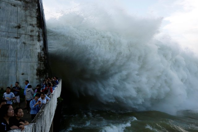 People watch as Hoa Binh hydroelectric power plant opens the flood gates after a heavy rainfall caused by a tropical depression in Hoa Binh province, outside Hanoi